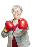 Senior woman wearing boxing gloves smiling Royalty Free Stock Images