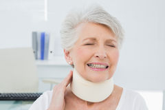 Senior woman wearing cervical collar with eyes closed. Closeup of a senior woman wearing cervical collar with eyes closed in the medical office royalty free stock photo