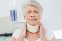Senior woman wearing cervical collar in medical office. Closeup of a senior woman wearing cervical collar with eyes closed in the medical office stock image