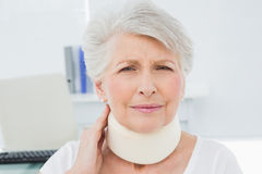 Senior woman wearing cervical collar in medical office. Portrait of a senior woman wearing cervical collar in the medical office royalty free stock images