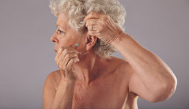 Senior woman wearing a hearing aid stock images