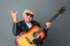 Senior woman in leather jacket and sunglasses studio standing on gray with guitar showing horns sign playful stock photos