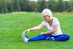 Senior woman stretching on green grass in park royalty free stock photo