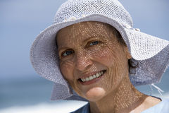 Senior woman wearing sun hat standing on beach, smiling, close-up, portrait Stock Images
