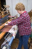 Senior Woman Weaving On Loom, Textile Artist. Active senior woman works on her loom to produce textile arts and weaving products Royalty Free Stock Images