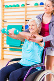 Senior woman in wheel chair doing physical therapy. Senior women in wheel chair doing physical therapy with her trainer Stock Image
