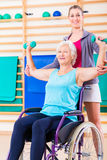 Senior woman in wheel chair doing physical therapy. Senior women in wheel chair doing physical therapy with her trainer stock photography