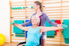 Senior woman in wheel chair doing physical therapy. Senior women in wheel chair doing physical therapy with her trainer royalty free stock photos