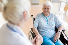 Senior woman in wheelchair with female doctor in hospital stock photos