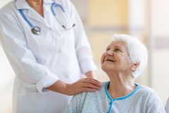 Senior woman in wheelchair with female doctor in hospital royalty free stock photo