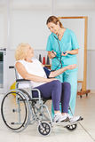 Senior woman in wheelchair getting blood pressure measurement Stock Photo