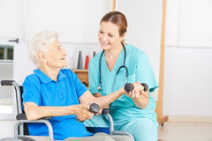Senior woman in wheelchair lifting dumbbells Stock Photo