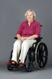 Senior woman in wheelchair over grey. Smiling senior woman seated in a wheelchair, either handicaped or disabled, looking at camera over neutral grey background Royalty Free Stock Images