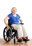 Senior woman in wheelchair over white. Smiling senior woman seated in a wheelchair, either handicapped or disabled, looking at camera over neutral white Stock Photos