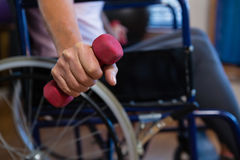 Senior woman in wheelchair performing exercise with dumbbell. In clinic Stock Photos