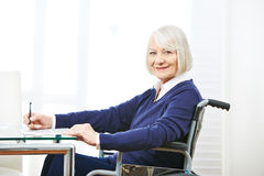 Senior woman in wheelchair on a table Stock Photo