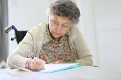 Senior woman in a wheelchair writing down notes Stock Photos