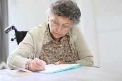 Senior woman in a wheelchair writing down notes Stock Photos