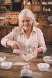 Senior woman whipping cream with whisk in glass bowl Stock Images
