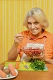 Senior woman eating vegetable salad. Senior woman in white apron eating vegetable salad Royalty Free Stock Photo