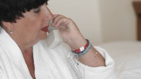 Senior woman in white bathrobe picks up the phone and takes a call. The concept of using technology and gadgets by