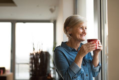 Senior woman at the window holding a cup of coffee Stock Image
