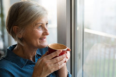 Senior woman at the window holding a cup of coffee Royalty Free Stock Image