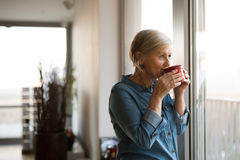 Senior woman at the window holding a cup of coffee Stock Photography
