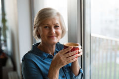 Senior woman at the window holding a cup of coffee Stock Photos