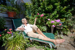 Senior woman with wineglass relaxing on lounge chair in garden Royalty Free Stock Images