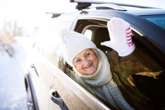 Senior woman in winter clothes in a car, waving Royalty Free Stock Photos