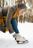 Senior woman in winter clothes putting on old ice skates. Stock Images