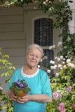 Senior Woman With Flower In Pot In Her Garden Stock Photo