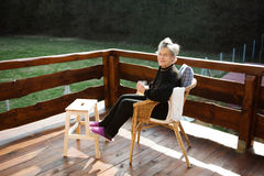 Senior woman on wooden terrace, resting with feet up. Beautiful senior woman at home, sitting on rattan chair on wooden terrace, resting with feet up on wooden stock image