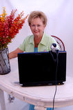 Senior woman working. A senior woman working and using a laptop computer webcam Stock Image