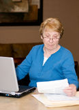 Senior woman working on computer. Senior lady working at the computer reading documents Stock Photo