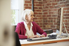 Senior Woman Working At Computer In Contemporary Office Stock Photos
