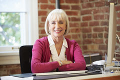 Senior Woman Working At Computer In Contemporary Office Stock Image
