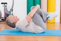 Senior woman working on exercise mat Stock Photo