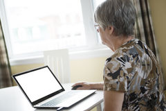 Senior woman working on her laptop in her kitchen Stock Image