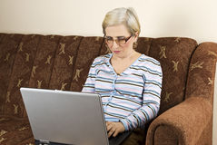Senior woman working on laptop. Senior woman using laptop home and sitting in sofa working,see more in People on couch Stock Photo