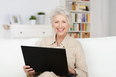 Senior woman working an a laptop. Balanced on her lap as she relaxes on a comfortable sofa at home smiling at the camera Royalty Free Stock Image