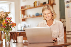 Senior woman working on a laptop in her kitchen. Positive senior woman smiling while typing on her laptop, while sitting at a rustic wooden table in a bright Royalty Free Stock Image