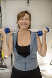Senior woman working out with dumbbells. At fitness center Stock Photography
