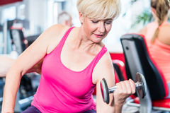 Senior woman working out with dumbbells at the gym Stock Photo