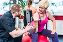 Senior woman working out with dumbbells with personal trainer Royalty Free Stock Images
