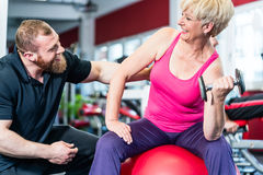 Senior woman working out with dumbbells with personal trainer. Senior women working out with dumbbells with personal trainer Royalty Free Stock Photo