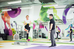 Senior woman working out in gym with her trainer Stock Image