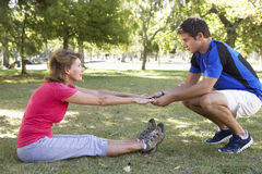 Senior Woman Working With Personal Trainer In Park Stock Photography