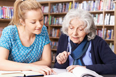 Senior Woman Working With Teacher In Library. Senior Woman Works With Teacher In Library royalty free stock images